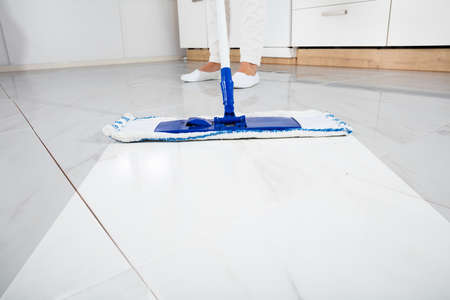 Low Section Of Person Wiping Floor With Mop In Kitchen Room Foto de archivo