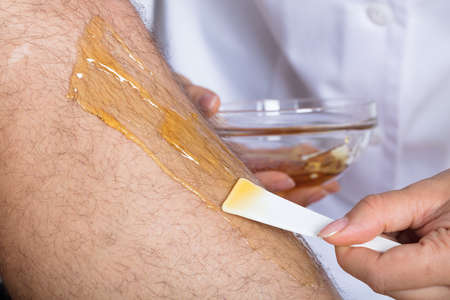 Close-up Of A Beauticians Hand Waxing Mans Leg Imagens