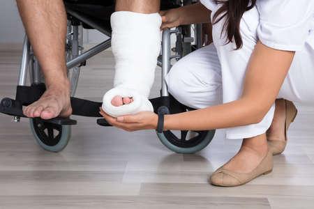 Close-up Van Een Vrouwelijke Arts Holding Gehandicapt Patient's Leg In Clinic