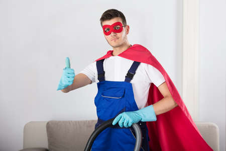 Superhero Janitor With Vacuum Cleaner Showing Thumb Up In Living Room