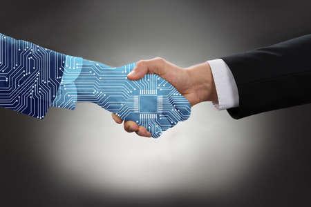 Nahaufnahme der digital erzeugten menschlichen Hand und des Geschäftsmannes, die Hände gegen Gray Background rütteln