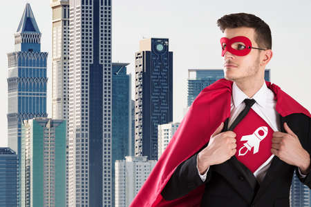 Young Businessman Opening Coat In Superhero Style Against City Buildings In Background