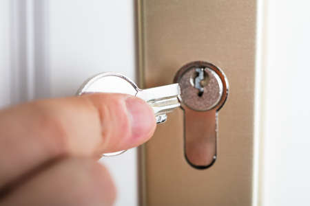 Close-up Of Person's Hand Holding Broken Key Inserting In Keyhole Stock Photo - 87562711