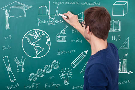 male teacher teaching physic equation on chalkboard in classroom