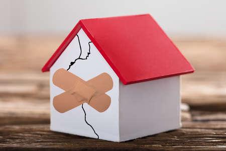 Modelo de casa rota con marca cruzada en el fondo de madera