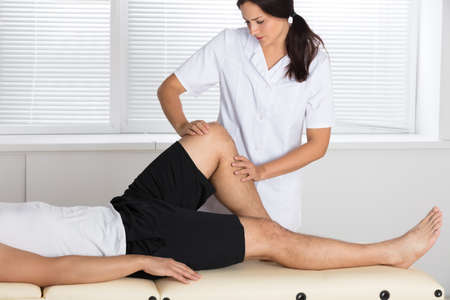 orthopedist: Young Female Physiotherapist Giving Leg Exercise To Patient In Clinic