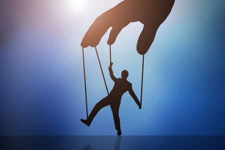 Close-up Of Persons Hand Controlling Puppet Man Against Blue Background