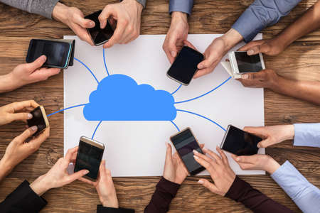 high tech: Group Of People Connecting Mobile Phones With Cloud Communication Network At Desk