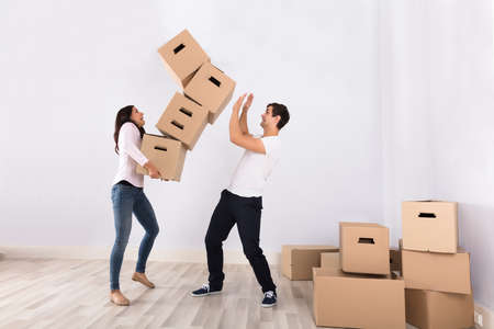 Young Woman Falling Stack Of Cardboard Boxes Over The Man In House Stock Photo