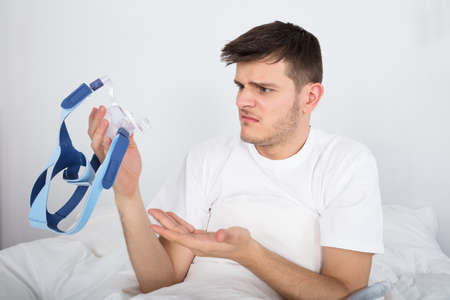Worried Young Patient Looking At CPAP Machine On Bed