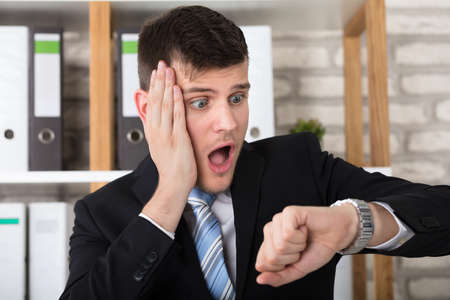 Close-up Of A Worried Young Businessman Checking Time In His Watch At Workplace