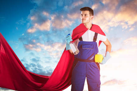 Young Janitor In Red Cape Holding Cleaning Equipments Against Cloudy Sky