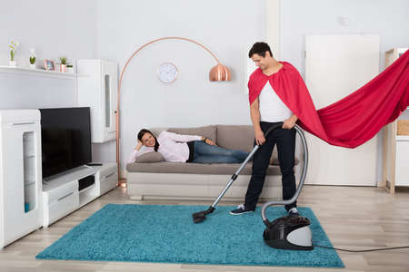 Happy Woman Lying On Sofa Looking At Her Husband Cleaning Carpet With Vacuum Cleaner