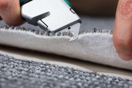 Carpenter Shaping Carpet Using Carpenter Tools To Lay Carpet At Home Фото со стока - 87895607