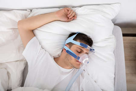 High Angle View Of Man Lying On Bed With Sleeping Apnea And CPAP Machine Stock Photo