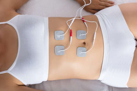 High Angle View Of A Woman Lying With Electrodes On Her Stomach