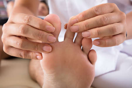 Close-up Of A Therapists Hand Treating Persons Foot In Clinic