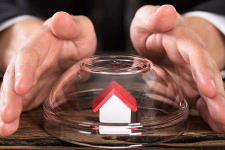Close-up Of Persons Hand Covering House Model In Glass Bowl