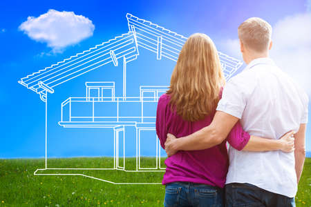 Rear View Of A Loving Couple Looking At Dream House Outdoor Stock Photo