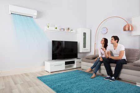 Lächelnde junge Paare, die auf Sofa unter Verwendung der Klimaanlage sitzen
