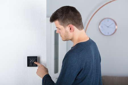 Jonge Man die Ruimtetemperatuur op een Digitale Thermostaat thuis aanpassen
