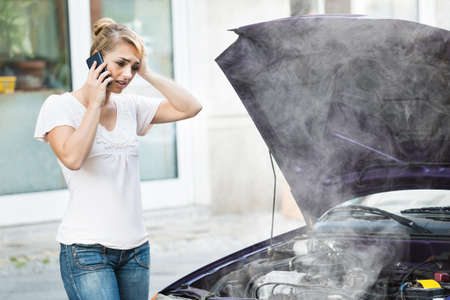 Young Woman Talking On Mobile Phone In Front Of Smokey Car Engine