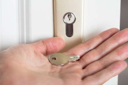 Close-up van de hand Persoon houden gebroken Key invoegen In Keyhole Stockfoto