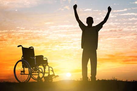 Silhouette Cudów Niepełnosprawnych Człowiek Walking Again Z Zachodu Słońca Zdjęcie Seryjne
