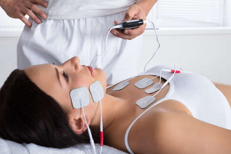 Close-up Of A Therapists Hand Giving Electrodes Therapy On Young Womans Chest And Face