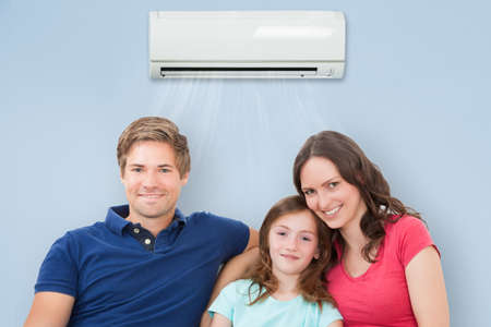Happy Family Sitting On Sofa Under Air Conditioning At Home Stock fotó
