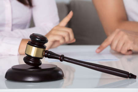 Couple Having Discussion Over Document Behind Gavel In Courtroom
