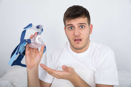 Close-up Of Shocked Young Man Holding CPAP Machine Mask Stock Photo