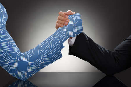 Close-up Of Digital Generated Human Hand And Business Man Arm Wrestling Against Grey Background