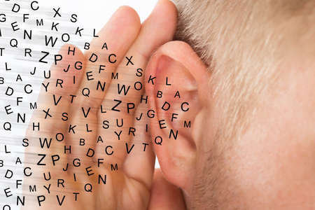 Man Holding Hand Near Ear And Listening Carefully Alphabet Letters Fly Stockfoto