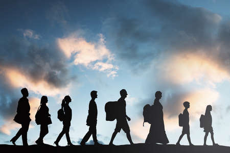Silhouette Of Refugees People With Luggage Walking In A Row 版權商用圖片 - 87895737