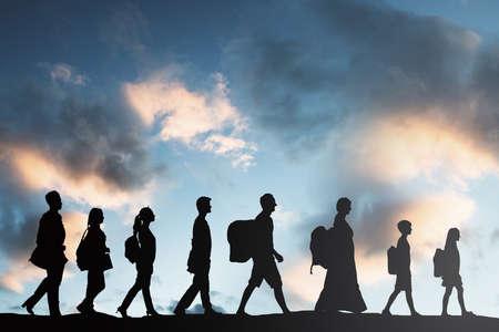 Silueta de los refugiados Personas con equipaje caminando en una fila Foto de archivo