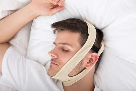 Young Handsome Man Sleeping With Anti Snoring Chin Strap On Head At Home Imagens