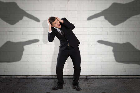 Shadow Hands On Wall Pointing Towards Scared Businessman