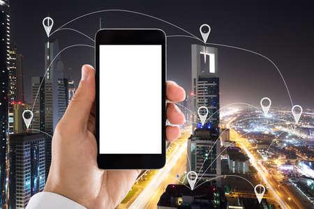 mano sosteniendo teléfono móvil con pantalla en blanco blanco en frente de la ciudad que muestra los punteros de destino Foto de archivo