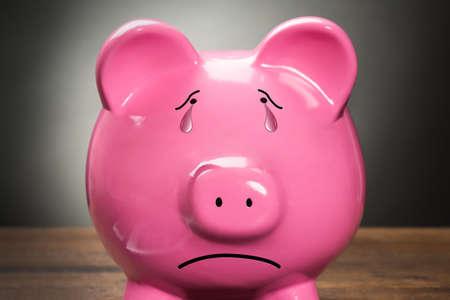 Close-up van een droevige roze spaarpot tegen grijze achtergrond