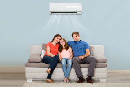 Happy Family Sitting On Sofa Under Air Conditioning At Home Stockfoto