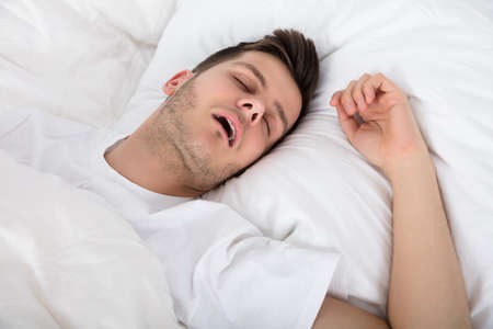 View Of Tired Young Man Snoring While Deep Sleeping In Bed Imagens