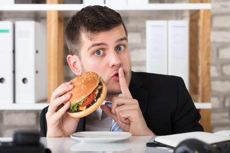 Portrait Of A Hungry Young Businessman Holding Burger With Finger On Lips In Office