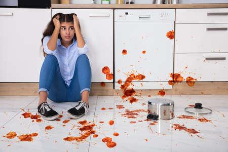 Donna infelice che si siede sul pavimento della cucina con alimento rovesciato in cucina Archivio Fotografico