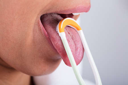 Photo Of Young Woman Cleaning Tongue With Cleaner Stock Photo