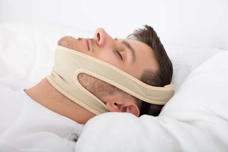 Young Handsome Man Sleeping With Anti Snoring Chin Strap On Head At Home Фото со стока
