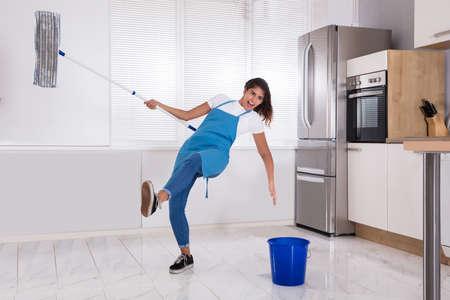 집에서 주방에서 바닥을 씌우고있는 동안 미끄러 져 여자 주부