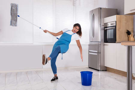 Woman Janitor Slipping While Mopping Floor In Kitchen At Home