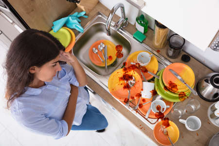 High Angle View Of Stressed Young Woman Looking At Unwashed Utensils In Kitchen