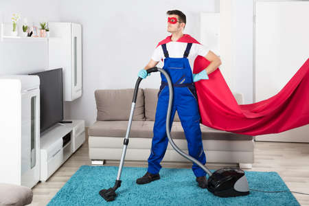 carpet stain: Superhero Janitor Cleaning Carpet With Vacuum Cleaner In Living Room